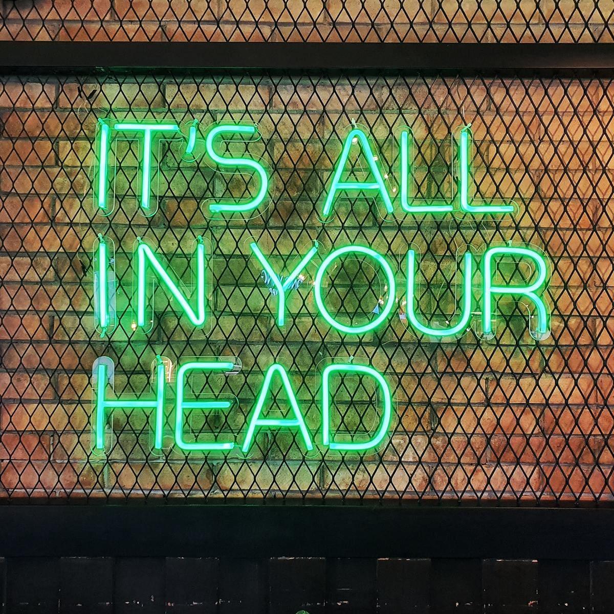 pared con neón con mensaje its all in your head